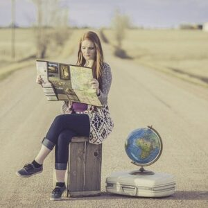 Woman Sitting on Suitcase Reading Map